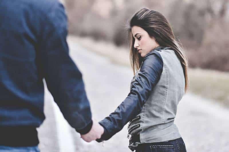 trauriges Paar Händchen haltend