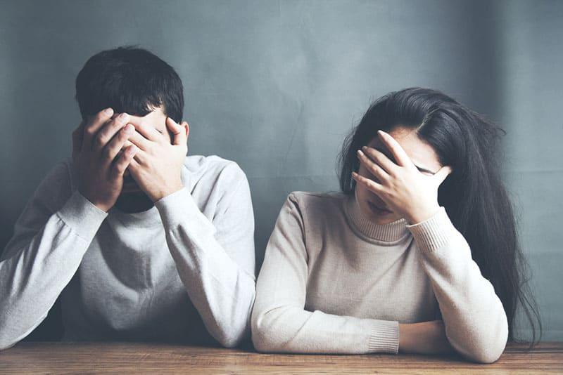 trauriges Paar hält ihre Hände auf den Gesichtern