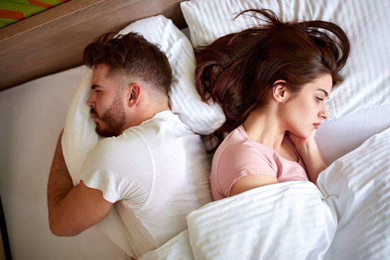 trauriges Paar im Bett liegen
