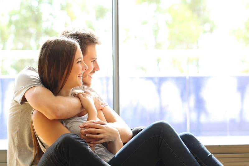 umarmtes Paar, das durch das Fenster schaut