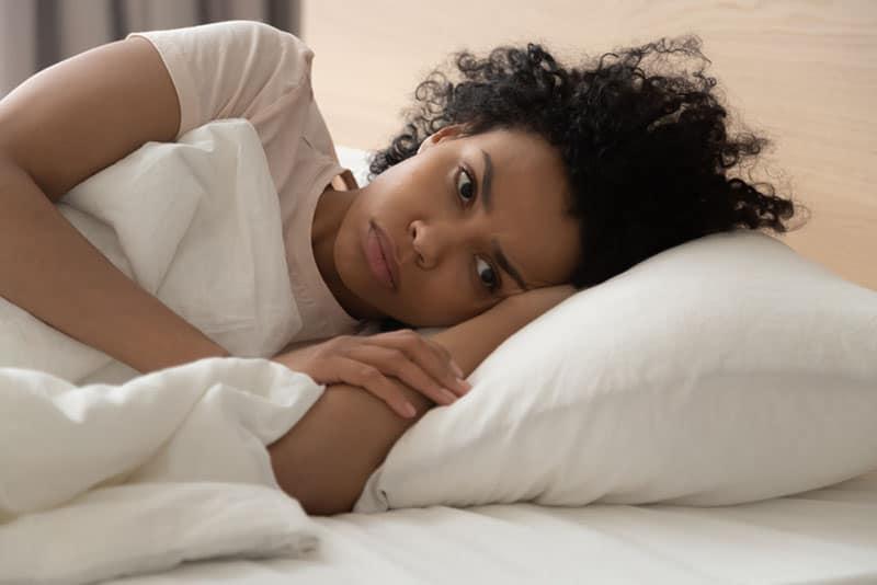 unglückliche Frau, die wach im Bett liegt