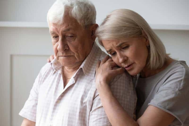 unglückliche Frau mittleren Alters tröstet depressiven älteren Ehemann