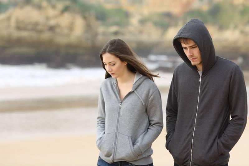 unglückliches Paar am Strand spazieren