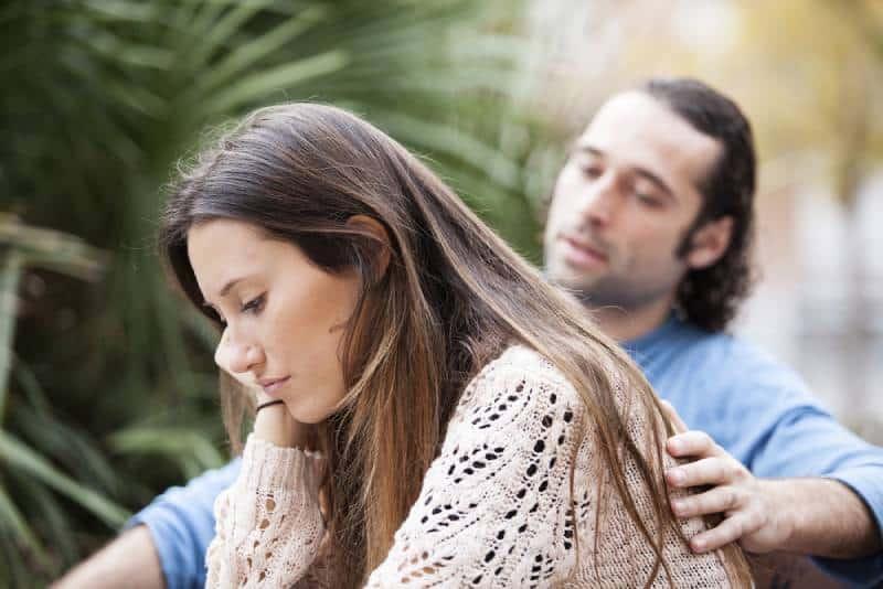 unglückliches Paar draußen sitzen