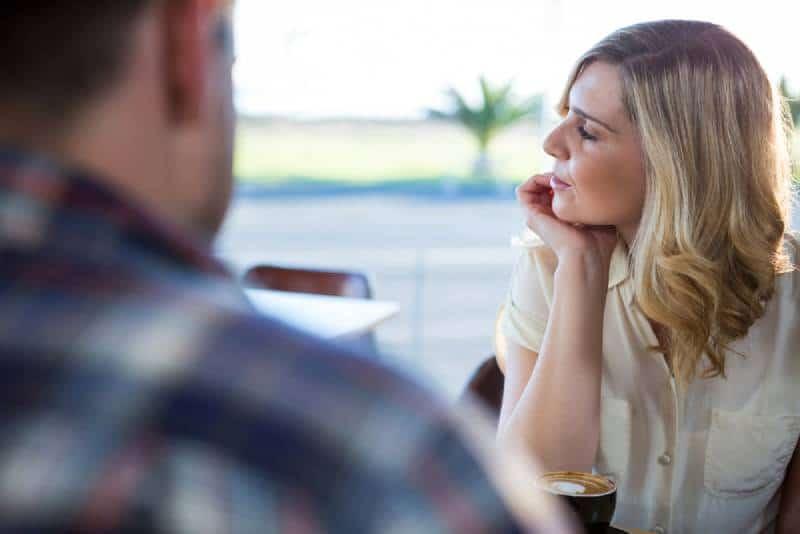 verärgerte Frau schaut weg, während sie mit Mann sitzt