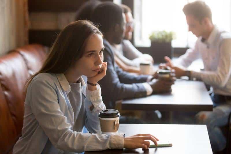 verärgertes Mädchen, das im Café sitzt