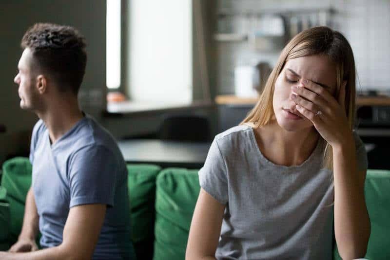 verärgertes Paar sitzt im Wohnzimmer