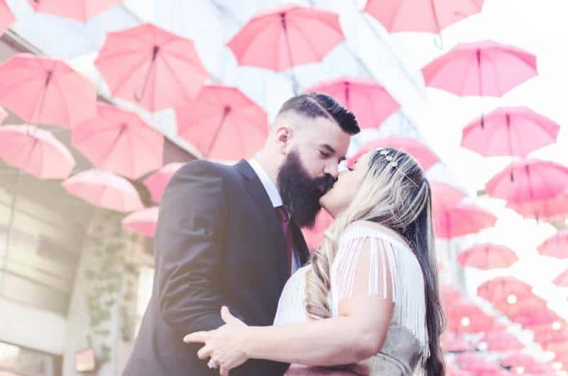 viel Regenschirm auf der Straße, Paar küssen und lieben