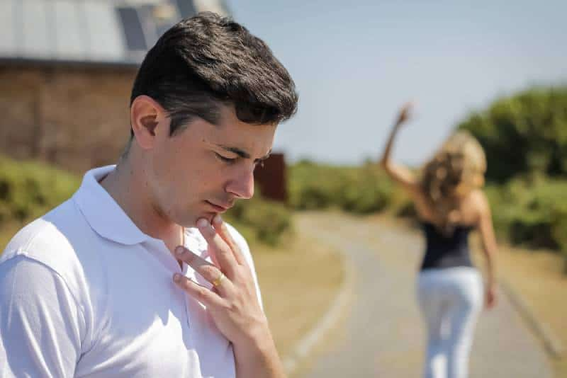 wütende Frau, die ihren besorgten Mann draußen lässt