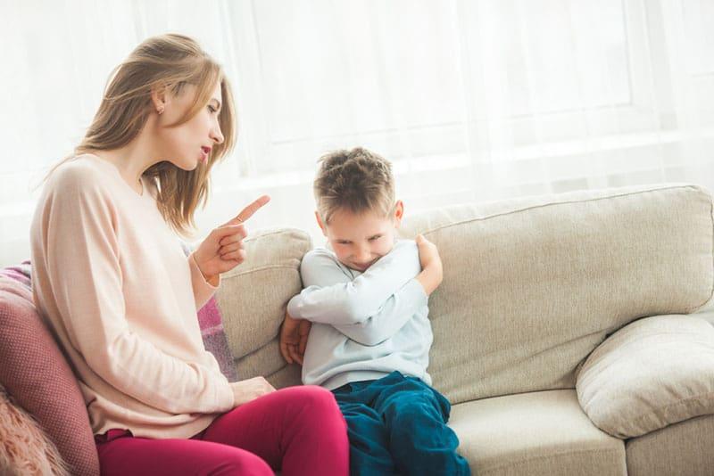 wütende Frau, die kleinen Jungen anschreit