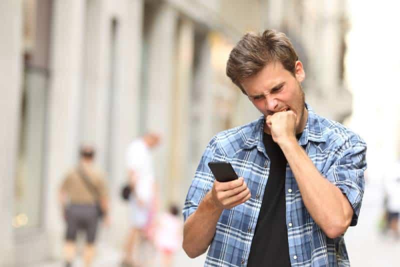 wütender Mann, der Telefon ansieht