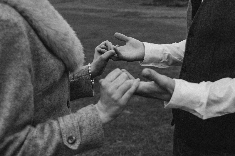 woman holding men's hands