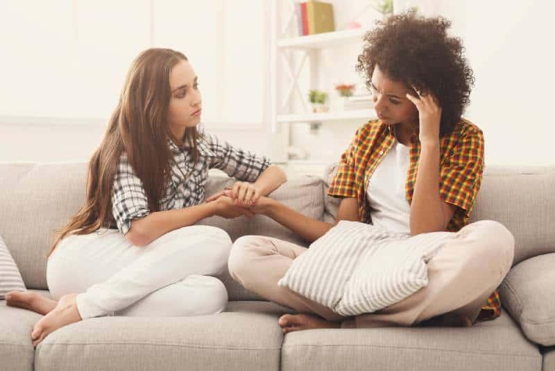 zwei Frauen, die über Probleme sprechen, während sie zu Hause auf dem Sofa sitzen