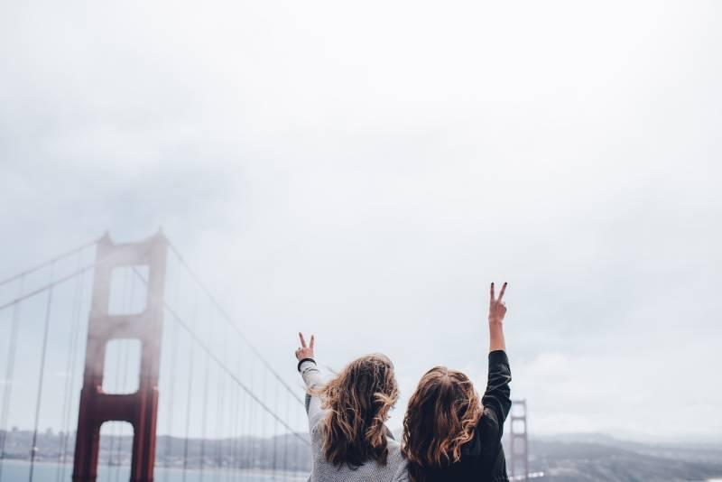 zwei Frauen, die Friedenszeichen nahe goldenem Tor machen