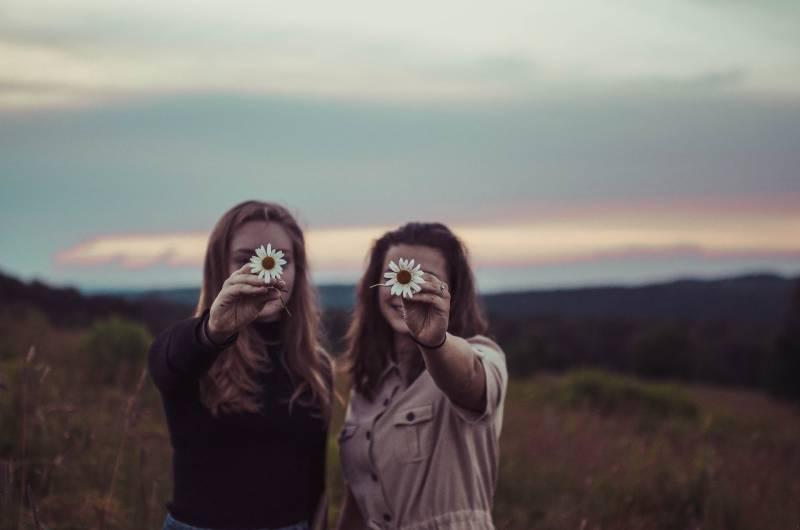 zwei Frauen halten Blumen