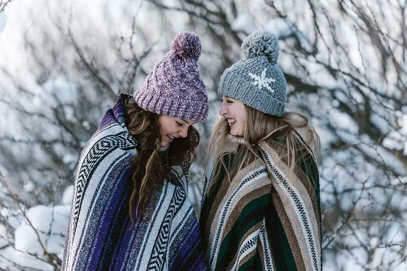 zwei Frauen in mehrfarbiger gestreifter Decke