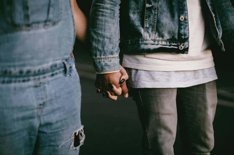 zwei Personen, die beim Gehen Hände halten