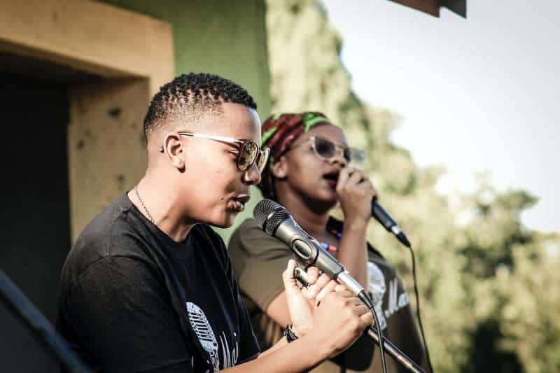 zwei Personen, die beim Sprechen Mikrofone halten