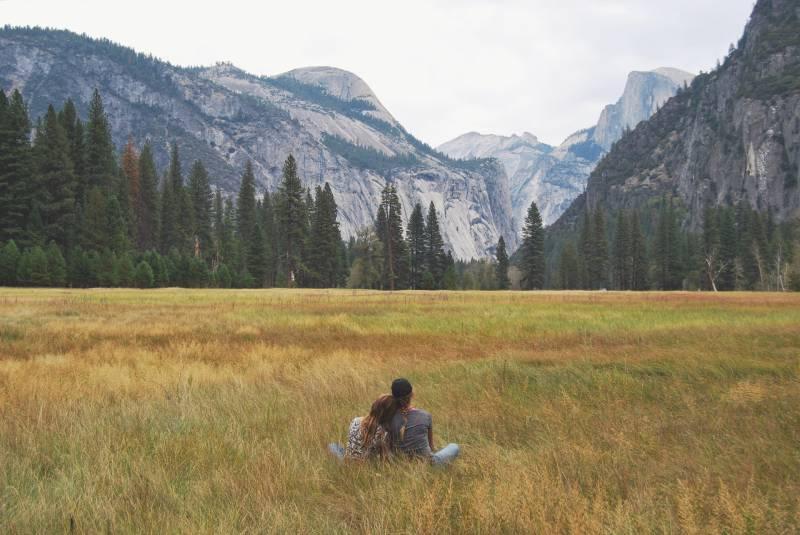 zwei Personen, die im Grasfeld sitzen und Berg betrachten