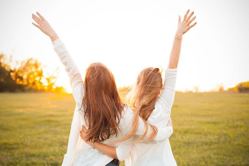 zwei Schwestern in Umarmung heben die Hand