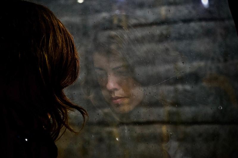 eine ängstliche Frau, die in der Nähe des Fensters steht