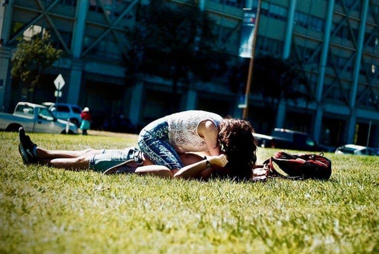 ein Mädchen sitzt auf einem Mann und küsst ihn