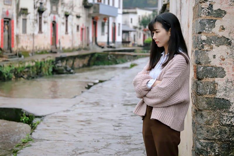 woman standing alone near brick wall