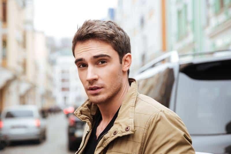 Bild des hübschen jungen Mannes, der auf der Straße geht und Kamera betrachtet.