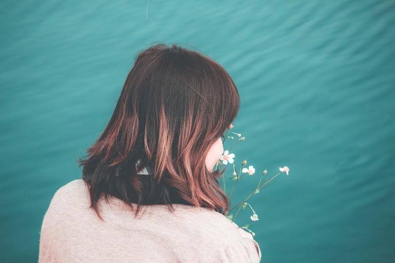 Das Mädchen schnüffelt an den Blumen am Wasser