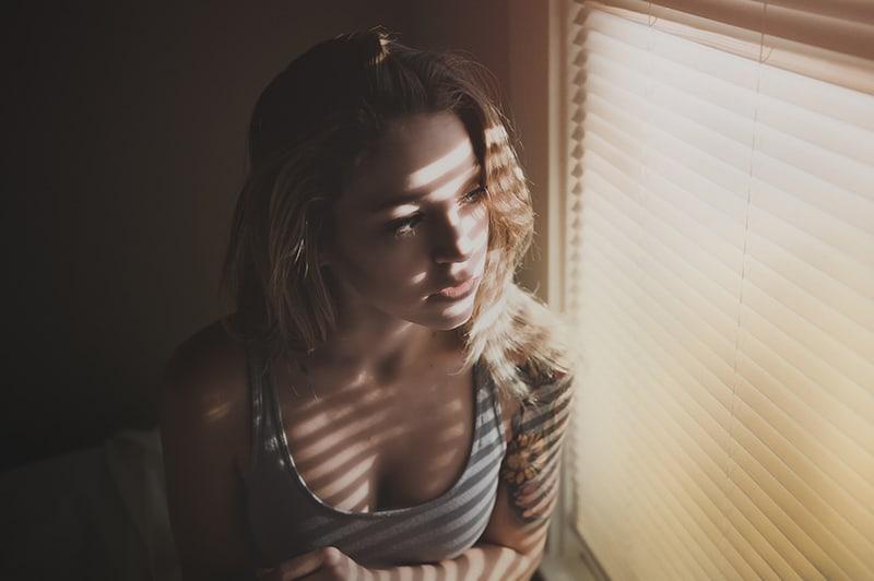 Frau in der Angst, die nahe Fenster steht