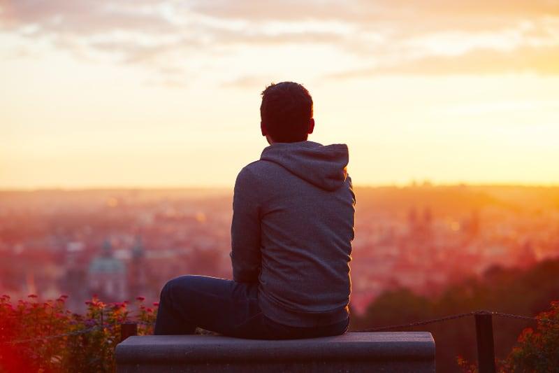Der junge Mann beobachtet den Sonnenaufgang