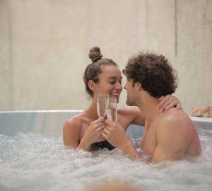 glückliches Paar, das Champagner im Whirlpool trinkt