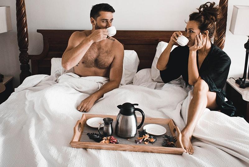 Die Frau bereitete dem Mann, der im Bett saß, Kaffee und Frühstück zu