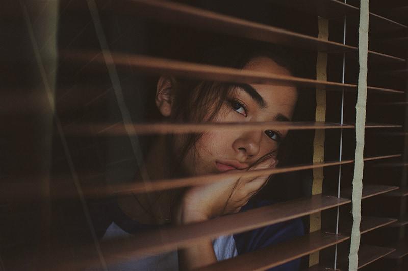 Die Frau kämpft mit ihren Gedanken, die in der Nähe des Fensters stehen