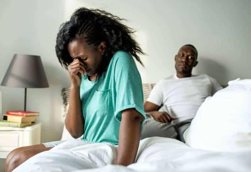 Die Frau weint und setzt sich neben den Mann, der liegt