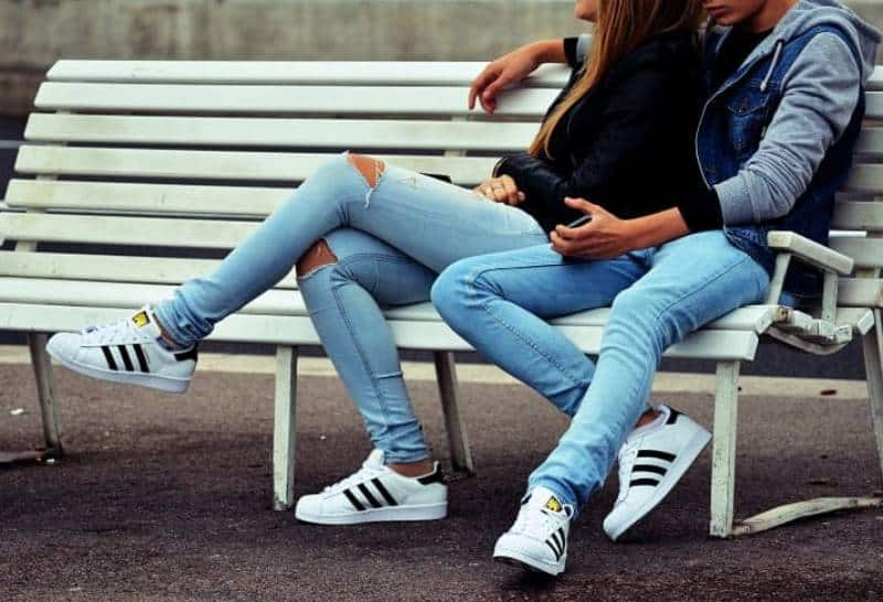 Draußen sitzt ein junges Liebespaar auf einer weißen Bank