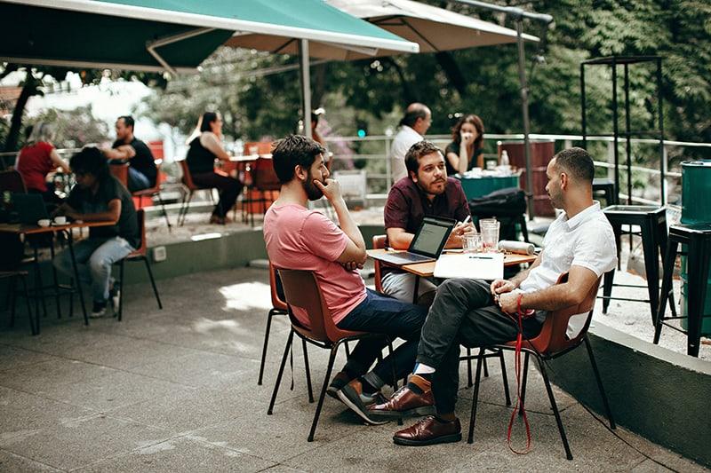 Drei Kollegen sitzen draußen und trinken
