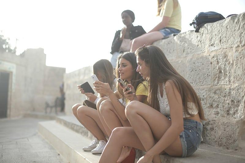 Drei Mädchen sitzen auf der Treppe während Sie ein Smartphone benutzen
