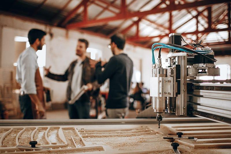 Drei Männer stehen in der Hobbywerkstatt beim Sprechen