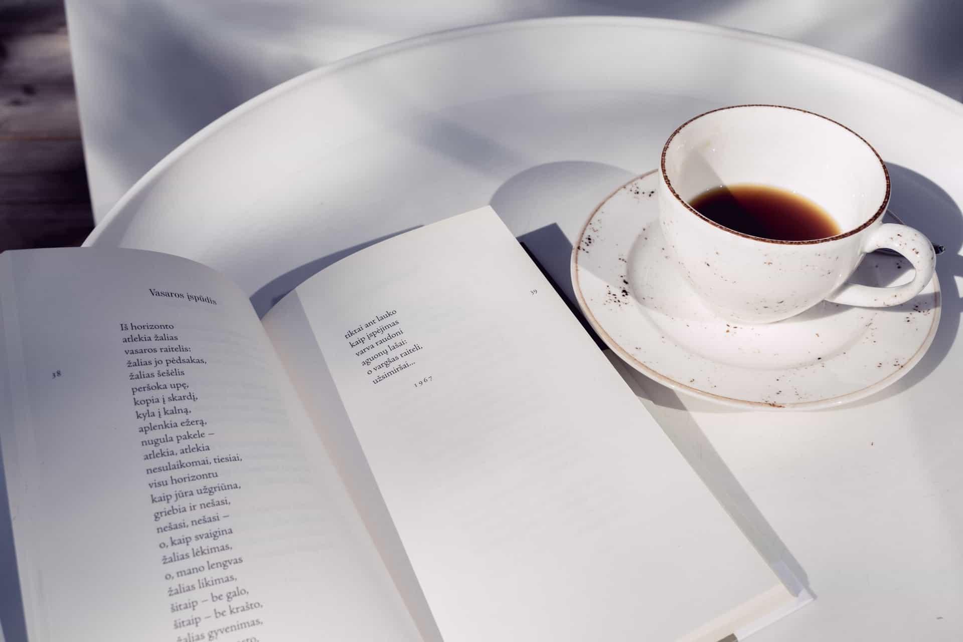 Ein Buch mit Gedichten auf einem Tablett neben Kaffee