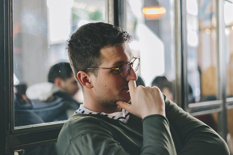 Ein Mann berührte seine Nase und dachte nach, während er in der Nähe der Glaswand saß