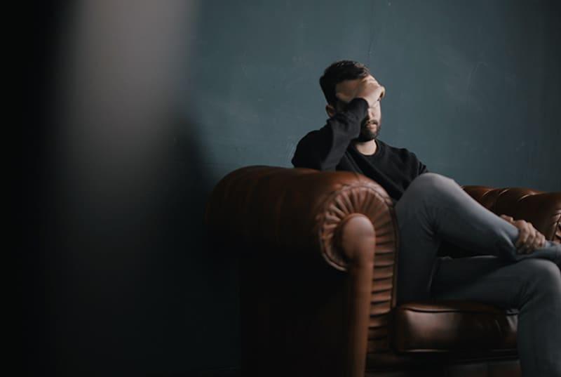 Ein Mann denkt nach, während er auf dem Sofa sitzt und seinen Kopf berührt
