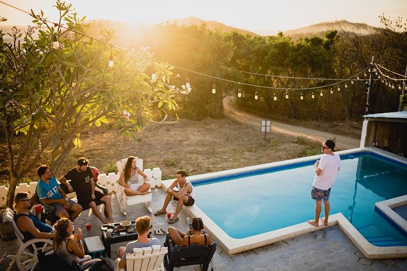 Ein Mann, der in der Nähe des Schwimmbades auf der Party mit Freunden während des Sonnenuntergangs steht