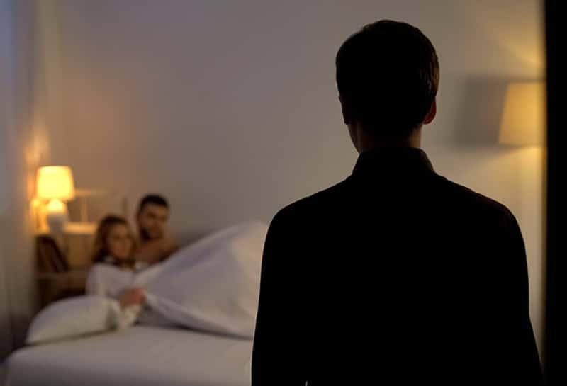 Ein Mann, der seine Freundin im Bett mit einem anderen Mann ansieht, während er vor ihnen steht