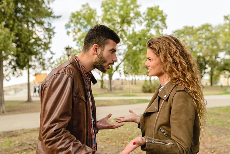 Ein Mann, der sich beleidigt fühlt, mit einer Frau zu streiten, während er im Park steht