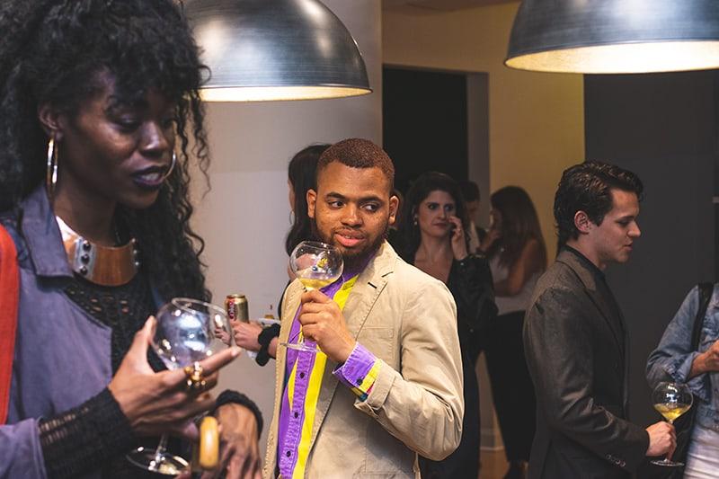 Ein Mann, der sich unwohl fühlt, wenn er auf der Party ein Glas Wein hält