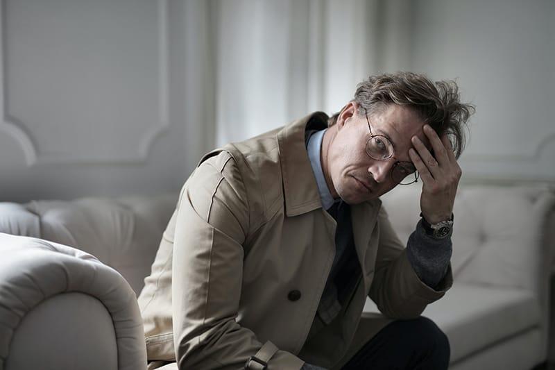 Ein Mann, der sich vernachlässigt fühlte, saß auf dem Sofa und berührte seine Stirn