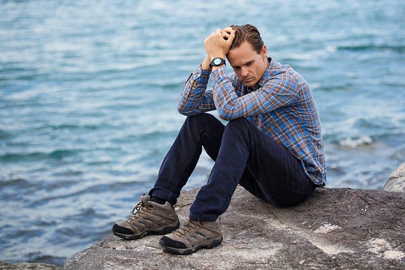 Ein Mann im Gefühlschaos sitzt auf dem Felsen in der Nähe des Gewässers