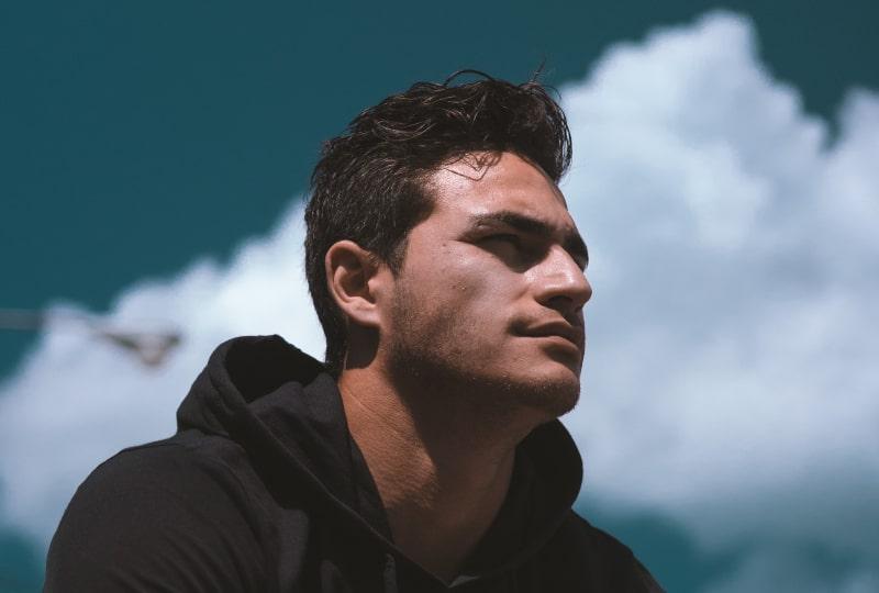 Ein Mann in einem schwarzen Sweatshirt schaut in die Ferne
