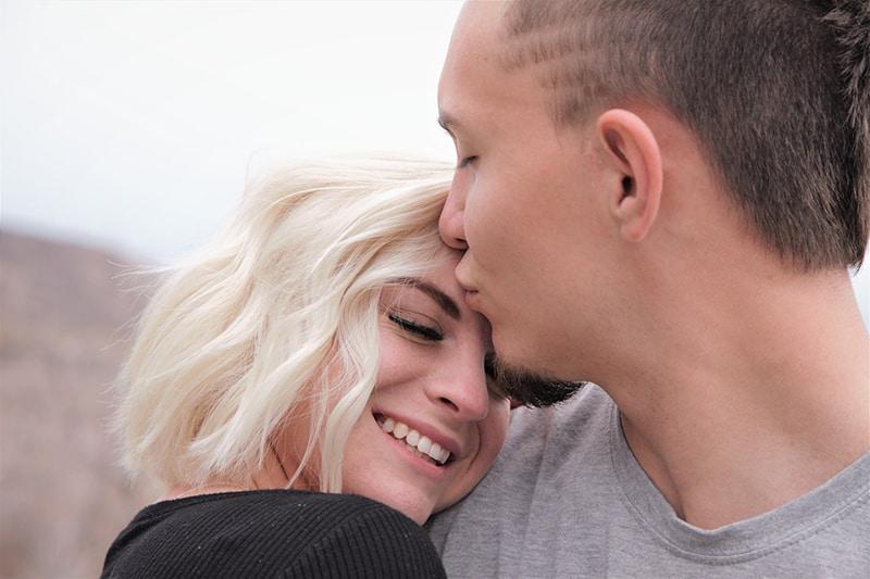 Ein Mann küsst die Stirn einer Frau, während er draußen steht